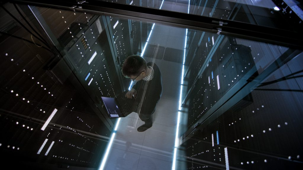 engineer on laptop working in data center
