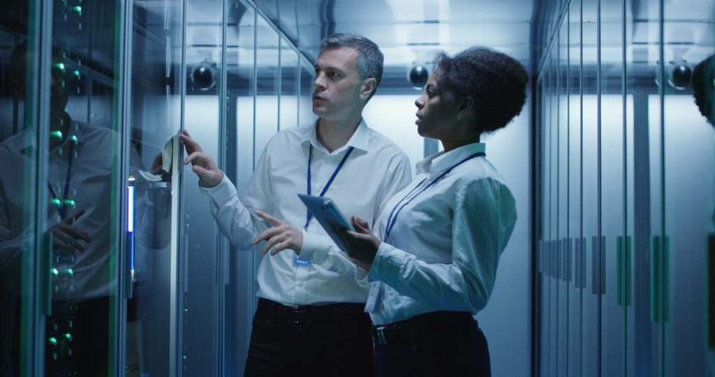 man and woman using devices diagnosing server hardware