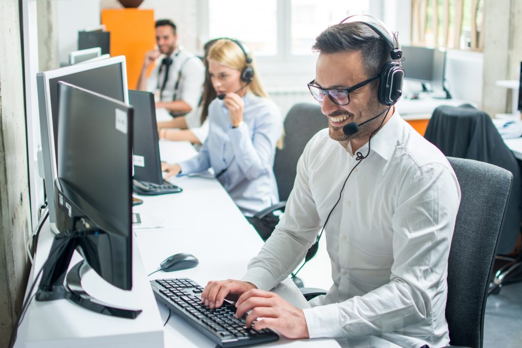 male technical support on telephone to client smiling