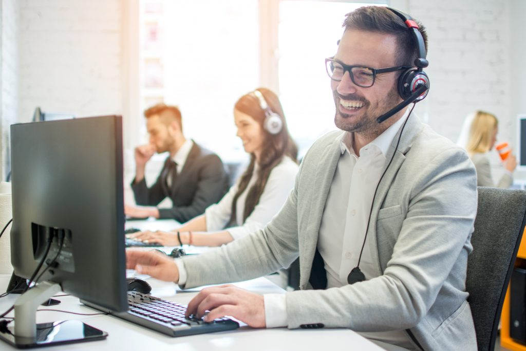cheerful technical operator with headphones talking to customer