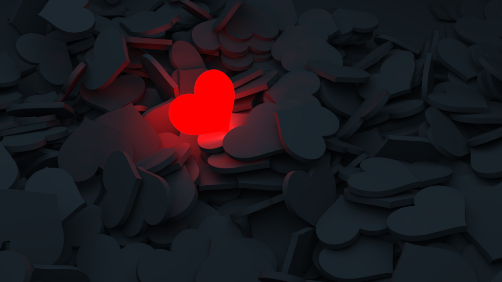 A lit up red heart in a sea of dark hearts